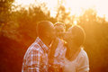 Happy family Mom and Dad holding daughter in his arms and kiss her in the park Royalty Free Stock Photo