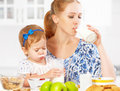Happy family mother and baby daughter at breakfast: biscuits with milk Royalty Free Stock Photo