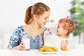 Happy family mother and baby daughter girl at breakfast: biscuit Royalty Free Stock Photo