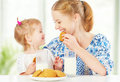 Happy family mother and baby daughter girl at breakfast: biscuits with milk Royalty Free Stock Photo