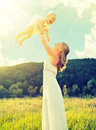 Happy family mother and baby daughter play on nature outdoors the green meadow in a white dress Stock Photos
