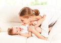 Happy family mother and baby daughter plays at home on the sofa Royalty Free Stock Photography