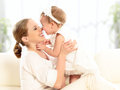 Happy family mother and baby daughter plays hugging kissing at home on the sofa Royalty Free Stock Photography
