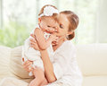 Happy family mother and baby daughter plays hugging kissing at home on the sofa Royalty Free Stock Photos