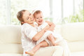Happy family mother and baby daughter plays hugging kissing at home on the sofa Stock Photo