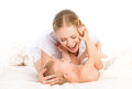 Happy family mother and baby having fun playing laughing on bed kissing the Royalty Free Stock Photography