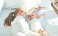 Happy family mother with baby playing and hug in bed Royalty Free Stock Photo