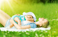 Happy family mother and baby are resting relax sleep outdoors on the grass in the summer park Stock Image