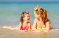 Happy family mother and chid daughter in masks on beach in summe Royalty Free Stock Photo