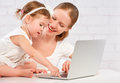 Happy family mother and child baby at home working on computer Royalty Free Stock Photo