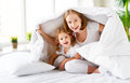 Happy family mother and child daughter laugh in bed Royalty Free Stock Photo