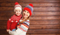 Happy family mother and child girl with christmas hat hugs at wo Royalty Free Stock Photo