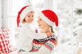 Happy family mother and child girl hugs at window at the winter Royalty Free Stock Photo