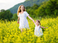Happy family, mother and child l little daughter running on mea Royalty Free Stock Photo