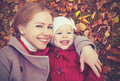 Happy family: mother and child little daughter play cuddling on autumn Royalty Free Stock Photo