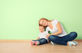 Happy family of mother and child sitting on the floor in an empt is a toddler empty home wall room Royalty Free Stock Photos