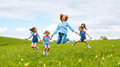 Happy family mother and children daughter girls laughing and jump on meadow in summer Royalty Free Stock Photo