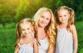 Happy family mother and children twin sisters on meadow in summe Royalty Free Stock Photo