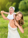 Happy family mother and daughter baby girl playing on nature outdoors Royalty Free Stock Photos