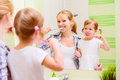 Happy family mother and daughter child brushing her teeth toothb girl toothbrushes front of the mirror in the bathroom Royalty Free Stock Photo