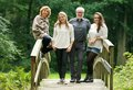 Happy family with mother father and daughters standing on bridge in the forest portrait of a Royalty Free Stock Image