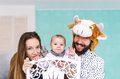 Happy family. Mother, the father in mask of a bull, baby son at home. Royalty Free Stock Photo