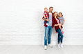 Happy family mother, father, son, daughter on a white blank wall Royalty Free Stock Photo