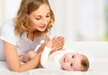 Happy family. mother playing with her baby in bed Royalty Free Stock Photo
