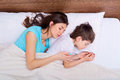 Happy family, mother, and son resting on the white bed. Sleeping Royalty Free Stock Photo