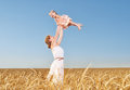 Happy family mother throws the baby into the sky in summer a wheat field Royalty Free Stock Photo