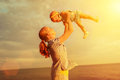 Happy family mother throws up baby in the sky nature Stock Image