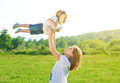 Happy family mother throws up baby in the sky nature Royalty Free Stock Images