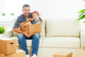 Happy family moves to new apartment dad and child daughter wit packs in cardboard boxes Royalty Free Stock Photo