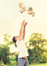 Happy family in nature. Dad throws up baby child Royalty Free Stock Photo