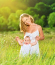 Happy family on nature mother and baby daughter outdoors the green meadow in a white dress Royalty Free Stock Photos