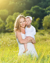 Happy family on nature mother and baby daughter outdoors the green meadow in a white dress Stock Photos