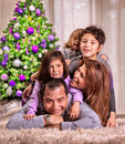 Happy family near christmas tree portrait of arabic lying down beautiful decorated celebrating holiday at home happiness concept Royalty Free Stock Photo