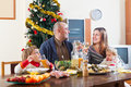 Happy family near christmas tree portrait of of four celebrating over holiday table at home Stock Photography