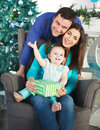 Happy family near the christmas tree with present Royalty Free Stock Photography