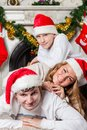 Happy family near christmas tree in santa claus hats lying at home Stock Photos
