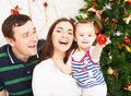 Happy family near the christmas tree smiling Royalty Free Stock Photo