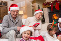 Happy family opening christmas gifts together at home in the living room Royalty Free Stock Photography