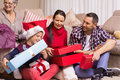 Happy family opening christmas gifts together at home in the living room Stock Photo