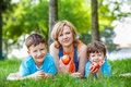 Happy family at outdoor caucasian in park laying in the grass with apple Royalty Free Stock Photo