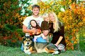 Happy family outside in autumn a of four people mother father child and baby are sitting the grass with their german shepherd dog Royalty Free Stock Images