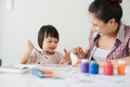 A happy family is painting. Mom help her daughter drawing Royalty Free Stock Photo