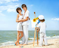 Happy family parents pose for child drawing picture on sea beach Stock Images