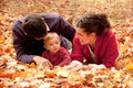Happy family at the park in autumn with baby lying fallen leaves Stock Image