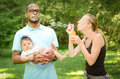 Happy family in the park interracial is blowing bubbles Stock Photos