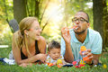 Happy family in the park interracial is blowing bubbles Royalty Free Stock Images